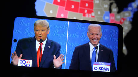 Donald Trump and Joe Biden are seen during the final presidential debate displayed on a screen of a smartphone
