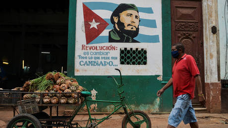 "A man wearing a face mask walks near a sign depicting Cuban late leader Fidel Castro and reading ""Revolution is to change everything that needs to be changed"", in Havana on May 13, 2020 © AFP / YAMIL LAGE"
