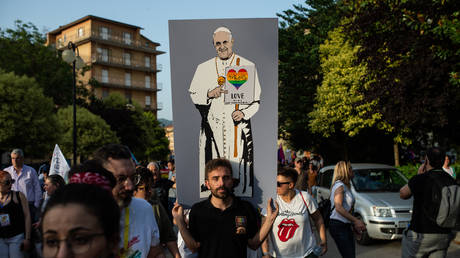 FILE PHOTO: An LGBT activist with a poster on which Pope Francis is drawn with a heart in the colors of the rainbow, during the Avellino Pride 2019 on June 15, 2019 in Atripalda, Italy