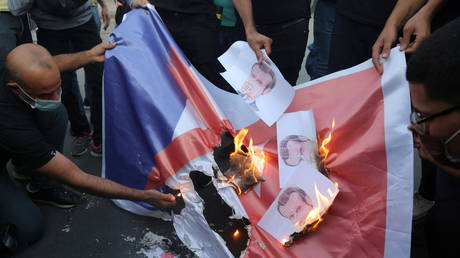 Iraqi people burn a French flag during a protest against the publications of a cartoon of Prophet Mohammad in France and French President Emmanuel Macron's comments, outside the French embassy in Baghdad, Iraq, October 26, 2020