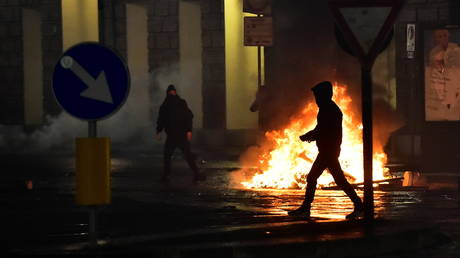 A fire is seen as people protest against new restrictions introduced by the Italian government to curb the coronavirus infections, in Turin, Italy, October 26, 2020.