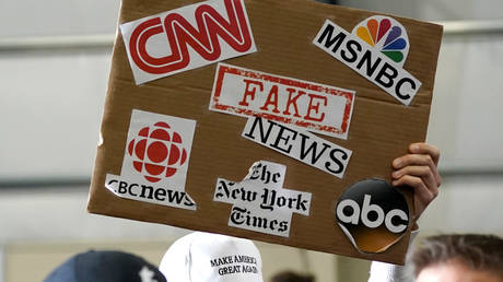 "A sign showing major news organizations along with the words ""fake news"" is held up as US President Donald Trump speaks at a Make America Great Again Rally in Washington, Michigan April 28, 2018."