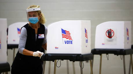 A woman cleans a voting booth at a polling station in Bel Air, Maryland, October 27, 2020.