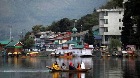 Women row a small boat in the waters of Dal lake, in Srinagar, September 17, 2019.
