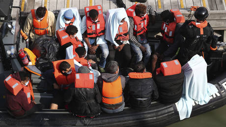 FILE PHOTO: A group of people, thought to be migrants wait on a Border Force rib to come ashore at Dover marina in Kent, England after a small boat incident in the English Channel, Tuesday Sept. 22, 2020.