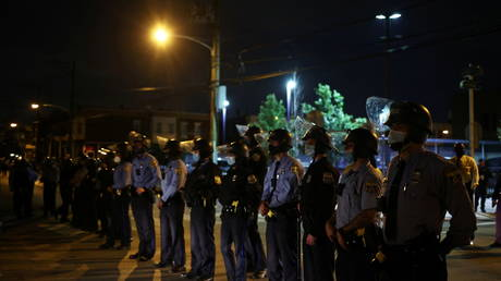 Officers stand guard outside a police station during protests over the death of Walter Wallace Jr at the hands of law enforcement, in Philadelphia, Pennsylvania, October 28, 2020.