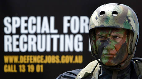 FILE PHOTO: A Special Air Services (SAS) soldier stands in front of a recruitment poster in Sydney October 20, 2003 after a demonstration of their skills as part of a public recruitment drive for more than 300 elite SAS troops by the defence force