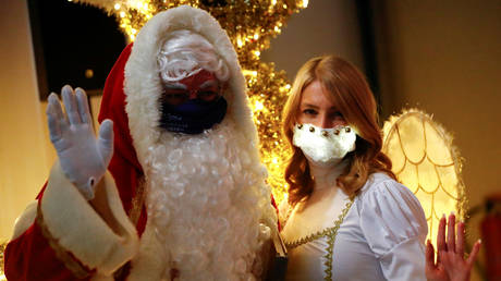 A man dressed as Santa Claus and woman dressed as angel wear face masks