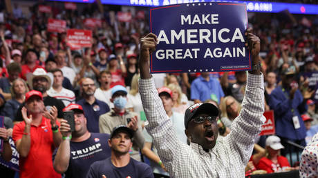 "A Black supporter of U.S. President Donald Trump holds up a ""Make America Great Again"" sign as the president arrives at his first re-election campaign rally in several months in the midst of the coronavirus disease (COVID-19) outbreak, at the BOK Center in Tulsa, Oklahoma, U.S., June 20, 2020"