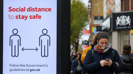 FILE PHOTO. A woman wearing a face covering walks past a 'Social Distance to stay safe' sign in north London, October 30, 2020.