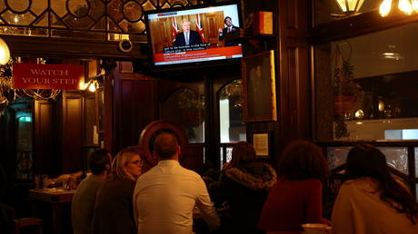 People watch Britain's Prime Minister Boris Johnson announce new lockdown measures inside a pub in Westminster, London, Britain, October 31, 2020. © Reuters / Henry Nicholls