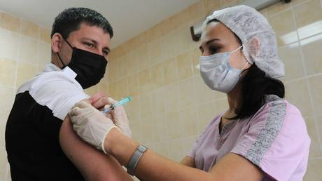 A man gets vaccinated at a clinic in the Tombov region, Russia. October 2020. © Sputnik / Aleksey Sukhorukov