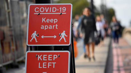 Pedestrians walk near public health signs in London, Britain, (FILE PHOTO) ©  REUTERS/Toby Melville/File Photo