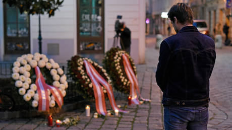 A pedestrian prays at the wreaths laid by the Austrian government at a crime scene in the city center the day after a deadly shooting spree on November 03, 2020 in Vienna, Germany