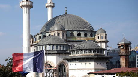 FILE PHOTO: A French flag flutters above the French Consulate, with a new mosque under construction in the background, in central Istanbul, Turkey