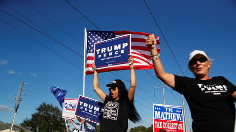Supporters of US President Donald Trump campaign near a polling station on election day, in Tampa, Florida, November 3, 2020.