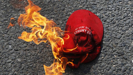 A Make America Great Again hat engulfed in flames burns on the ground after counter protesters lit it on fire in front of the barricade.
