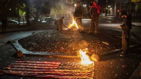 A small group of racial justice protesters watch a burning American Flag as they gather in front of the Multnomah County Justice Center early in the morning on November 4, 2020 in Portland, Oregon