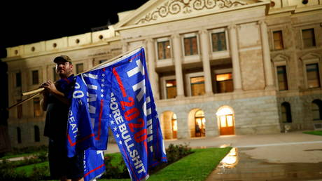A Trump supporter holds flags as he stands in front of the Arizona State Capitol Building in Phoenix, Arizona November 4, 2020.
