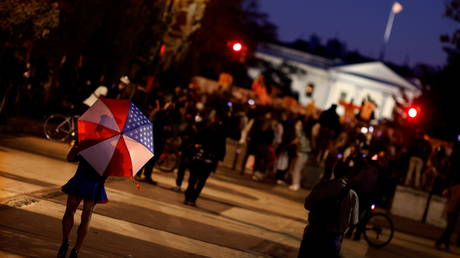 A person with an umbrella in the colors of the U.S. flag walks into a gathering of local residents waiting for the results of the 2020 presidential election outside of the White House in Washington, U.S., November 4, 2020