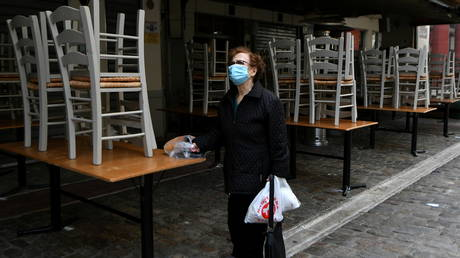 File photo: A woman stands outside a closed restaurant, amid the Covid pandemic, in Thessaloniki, Greece on October 30, 2020 © REUTERS/Alexandros Avramidis