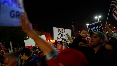 Supporters of U.S. President Donald Trump hold signs as they gather in front of the Maricopa County Tabulation and Election Center (MCTEC) to protest about the early results of the 2020 presidential election, in Phoenix, Arizona November 4, 2020.