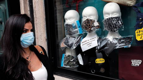 A woman wearing a mask walks past a shop where protective face masks are displayed during the Covid-19 pandemic in Italy. © Reuters / Remo Casilli