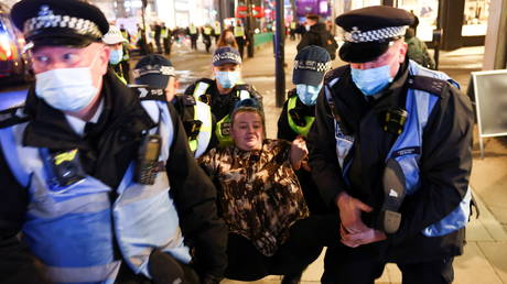A woman is detained by police officers as protestors from the Million Mask March and anti lockdown protestors demonstrate, amid the coronavirus (COVID-19) outbreak in London, Britain November 5, 2020.