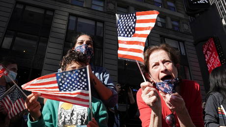 People react as media announce that Democratic US presidential nominee Joe Biden has won the US presidential election, on Times Square in NYC.