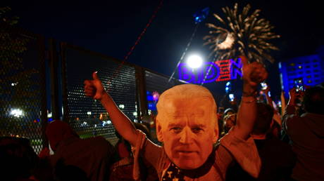 FILE PHOTO: A supporter wearing a mask of U.S. President-elect Joe Biden gives thumbs-up during fireworks after Biden's victory speech, in Wilmington, Delaware, U.S. November 7, 2020