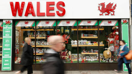 FILE PHOTO: Britain, Cardiff, Wales - People walk past a souvenir shop in Cardiff