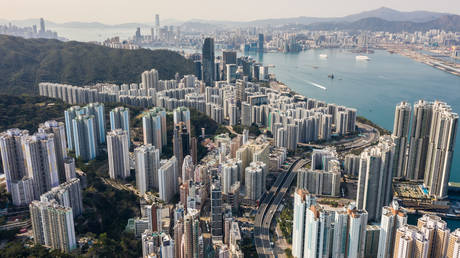 FILE PHOTO An aerial view shows residential and commercial buildings on Hong Kong island (foreground and top L) and Kowloon (top C and R), either side of Victoria Harbour, on February 17, 2020. © AFP / Anthony WALLACE