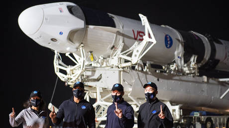 L to R: NASA astronauts Shannon Walker, Victor Glover, Mike Hopkins and Soichi Noguchi of JAXA pose in front of the SpaceX Falcon 9 rocket and Crew Dragon spacecraft
