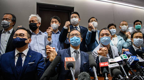 Opposition lawmakers join hands at a press conference in a Legislative Council office in Hong Kong on November 11, 2020. © AFP / Anthony Wallace
