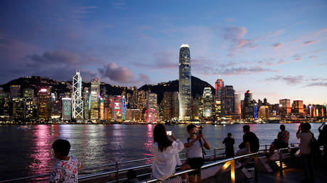FILE PHOTO: People enjoy the sunset view with a skyline of buildings during a meeting on national security legislation, in Hong Kong, China June 29, 2020
