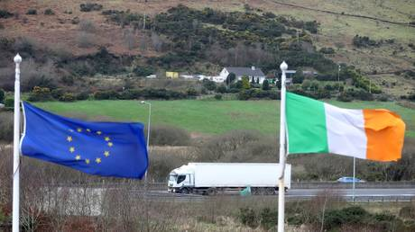 FILE PHOTO: The European Union flag and national flag of Ireland on the border road between Dundalk, Ireland, and Newry in Northern Ireland. February 2020. ©  AFP / Paul Faith
