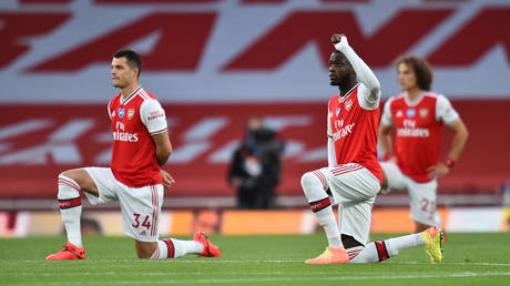Arsenal players take a knee before their game against Liverpool in July. © Reuters