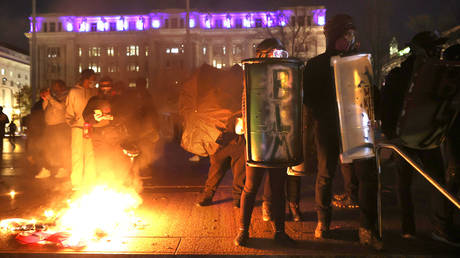 """Black Lives Matter protesters hold shields as they stand next to a small fire during a protest following the """"Million MAGA March"""" from Freedom Plaza to the Supreme Court, on November 14, 2020 in Washington, DC"""