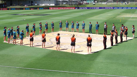 The Australian and New Zealand women's teams stand barefoot with an Indigenous silk prior to their game in Brisbane in September. © Getty Images