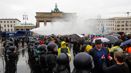 Demonstrators are sprayed with a water cannon during a protest against the government's coronavirus disease (COVID-19) restrictions, next to the Brandenburger Gate in Berlin, November, 18, 2020.