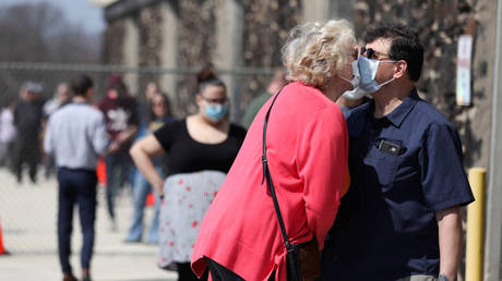 FILE PHOTO: Wisconsin residents kiss while wearing face masks as they wait in line outside a polling station, in Milwaukee, Wisconsin.
