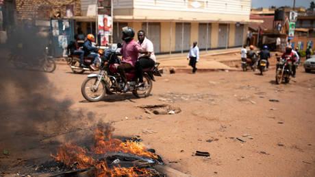Le trafic passe devant un barrage routier de manifestants le 19 novembre 2020 à Kampala, en Ouganda.