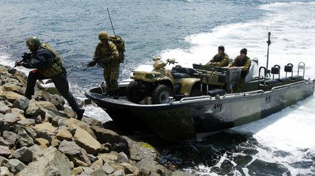 FILE PHOTO: Special Air Services (SAS) soldiers disembark from their amphibious carrier on Sydney Harbour October 20, 2003 during a public recruitment drive