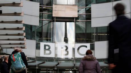 Pedestrians walk past a BBC logo at Broadcasting House, London, UK