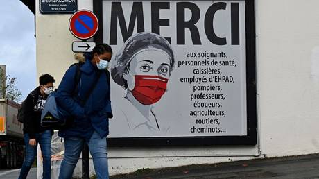 People walk past a poster featuring a nurse on a street in Rennes, western France on November 2, 2020 © AFP / Damien MEYER