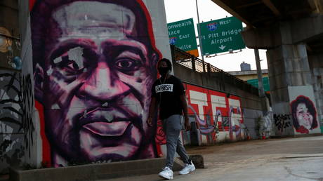 FILE PHOTO: A man wearing a protective face mask walks by murals of George Floyd and Breonna Taylor amid the coronavirus disease (COVID-19) pandemic in Pittsburgh, Pennsylvania, U.S., October 21, 2020