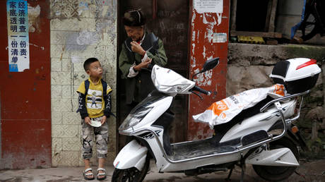 A child stands next to an old man on the street in Ganluo county of Liangshan Yi Autonomous Prefecture, Sichuan province, China