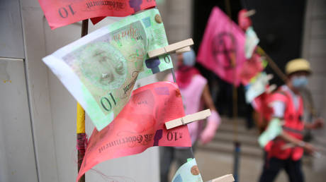 """FILE PHOTO: Fake banknotes, called """"dirty money"""", are seen as Extinction Rebellion climate activists stage a protest during a """"peaceful disruption"""" of UK parliament as lawmakers return from the summer recess, London, Britain September 9, 2020"""