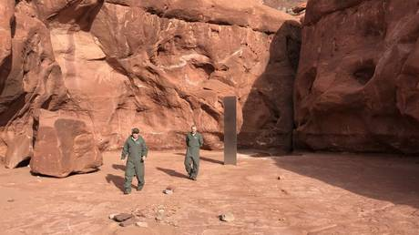 Utah state employees inspect an unexplained 'monolith' discovered in a remote stretch of desert.