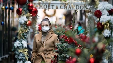 A woman wears a mask as she walks past Christmas-themed window displays in London. November 23, 2020. © AFP / Tolga Akmen